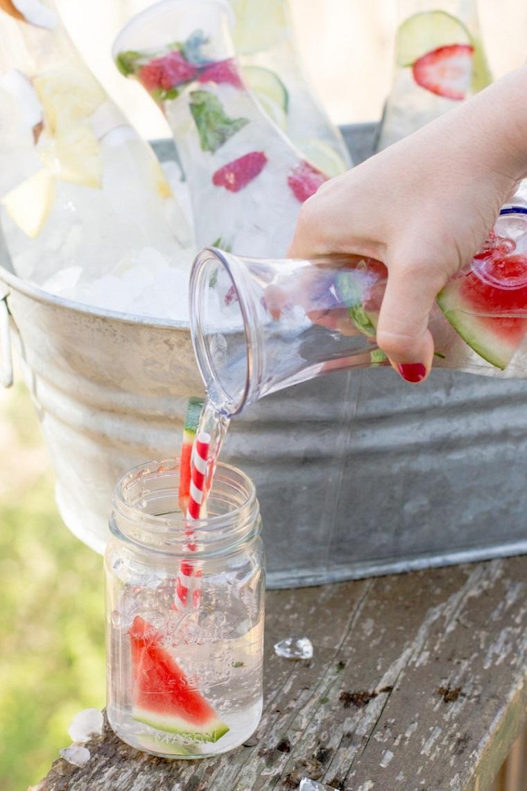 Caraffe di vetro con acqua e frutta, bevanda sgonfia pancia in un barattolo di vetro