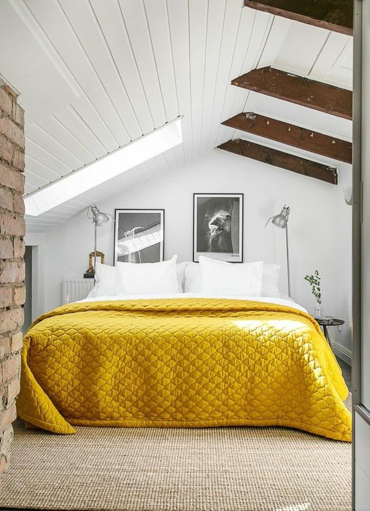 piccola mansarda adibita a camera da letto con muro con mattoni a vista, quadri e travi in legno