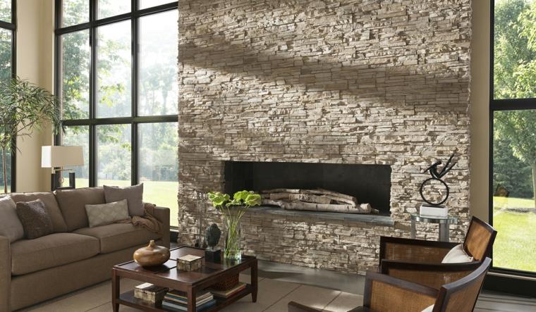 elegante salotto arredato con un divano color tortora, tavolino in legno con ripiano e parete in pietra con camino