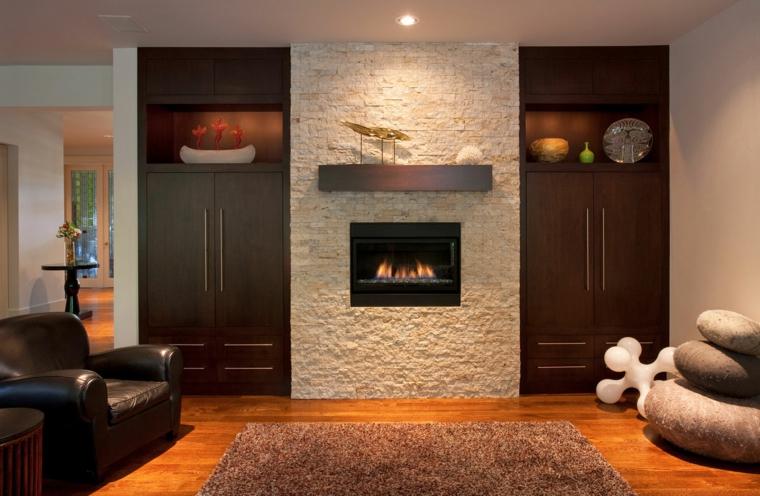 elegante salotto arredato con degli armadi a parete in legni, un camino moderno all'interno di una parete in pietra
