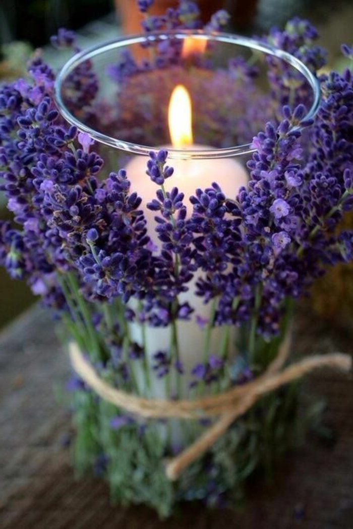Decorazioni tavola con una candela decorata con fiori di lavanda legati con nastro
