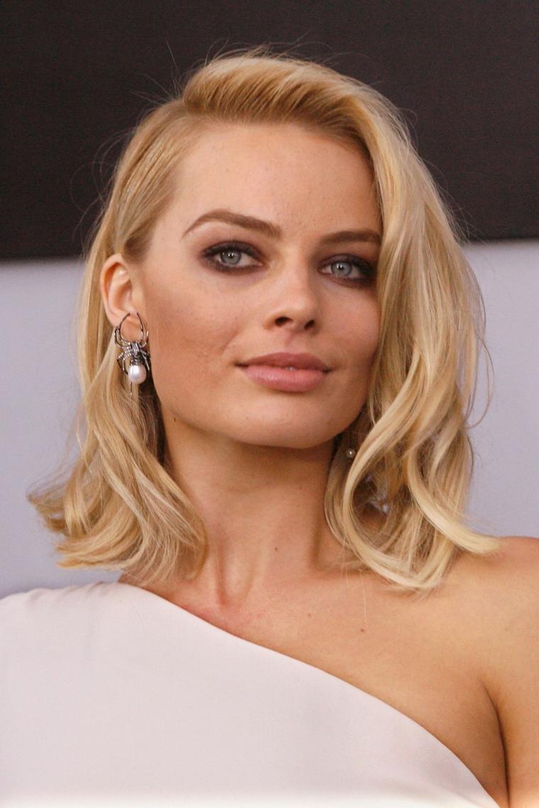 Idea per dei tagli capelli donna di colore biondo, acconciatura con riga laterale e mosso sulle lunghezze
