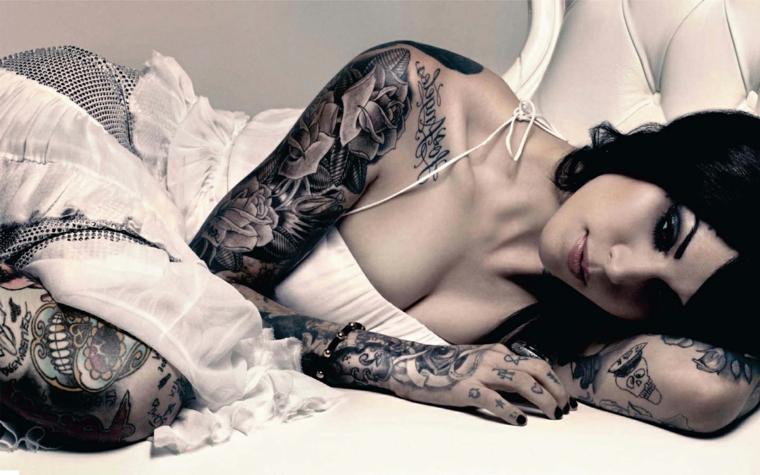 bellissima ragazza sdraiata con numerosi tatuaggi fra cui alcuni tattoo rose sulle braccia