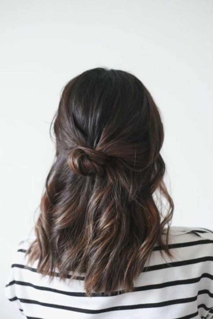 ragazza con un semi raccolto a chignon, capelli castani ondulati, un'idea per acconciature facili