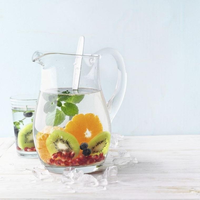Acqua detox per dimagrire, caraffa di vetro con frutta tagliata a pezzettini