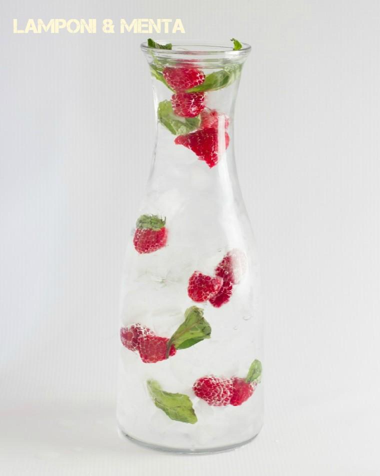 Acqua detox per dimagrire, caraffa di vetro con tanti lamponi e foglie di menta