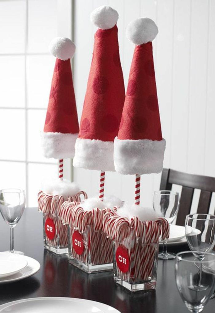 Centrotavola con dei bicchieri di vetro e caramelle all'interno, cappucci di Babbo Natale di feltro rosso