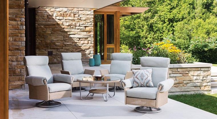 Alberi da giardino sempreverdi e un arredamento con mobili in rattan di colore grigio e beige