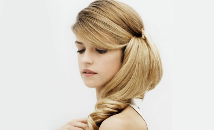 ragazza bionda con i capelli lunghi, acconciature facili e veloci con una morbida coda a lato