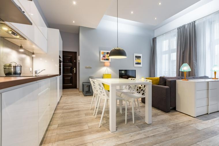funzionale e raccolto open space con cucina lineare e tavolo bianchi, divano grigio e parquet