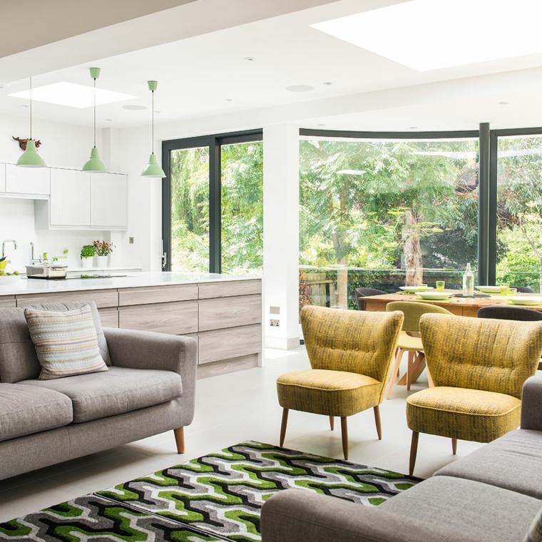 pavimento chiaro. cucina soggiorno open space con mobili della cucina bianchi e grigi, divano grigio e tappeto con inserti verdi