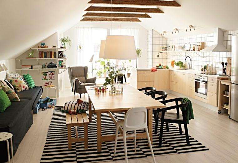 stanza piccola con cucina soggiorno open space con mobili della cucina in legno chiaro e divano grigio
