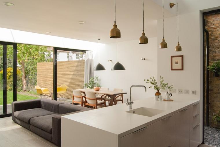 come arredare cucina soggiorno ambiente unico con pareti bianche, isola con cassetti e lavabo, divano grigio e tavolo da pranzo