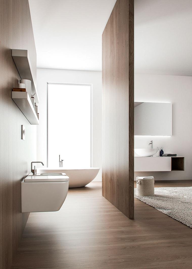 Bagni moderni con rivestimento di legno, sanitari sospesi di colore bianco, pannello per separare il bagno