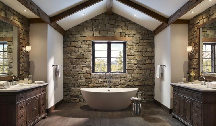 ampio bagno in stile rustico con mobili in legno, vasca bianca e muri ricoperti di pietra