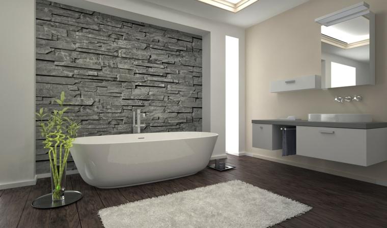 bellissimo bagno moderno con parete in pietra, vasca bianca e mobili sospesi