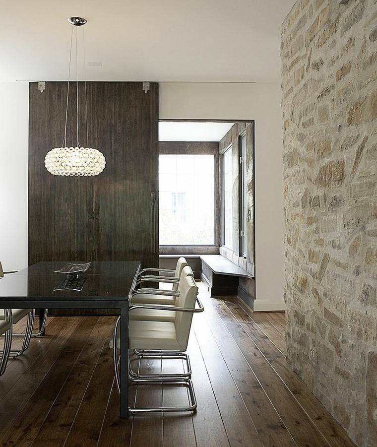 elegante sala da pranzo con tavolo rettangolare e sedie in pelle bianca con parete in pietra