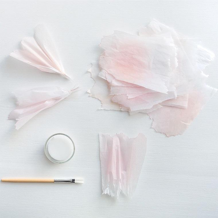 Carta crespa di colore bianco incollata in un'estremità, pennello e colla bianca vinilica