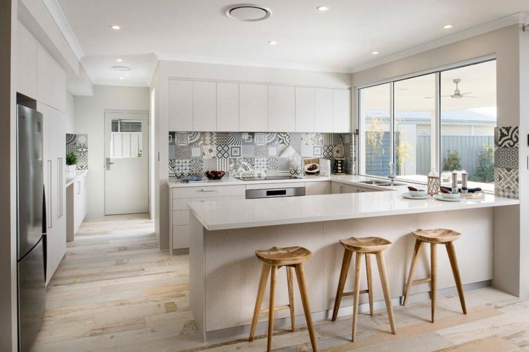 moderna cucina a vista con mobili a u bianchi, tre sgabelli in legno e paraschizzi a mosaico