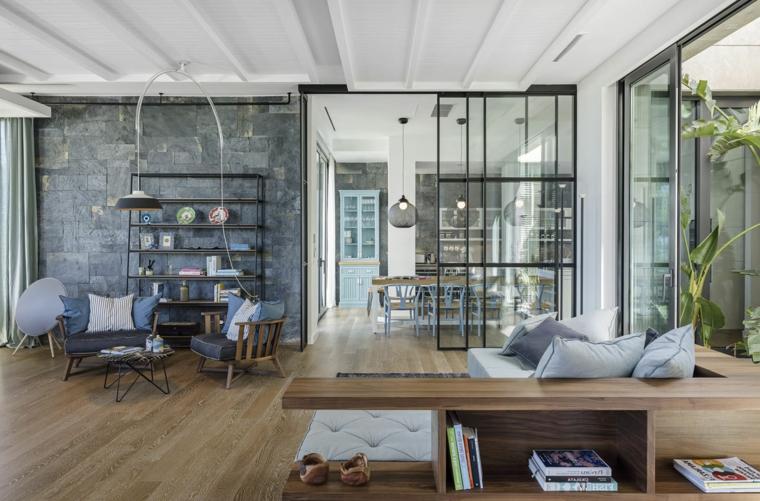 moderno open space con pavimento in parquet, divani e poltrone, una grande vetrata parete interna in pietra