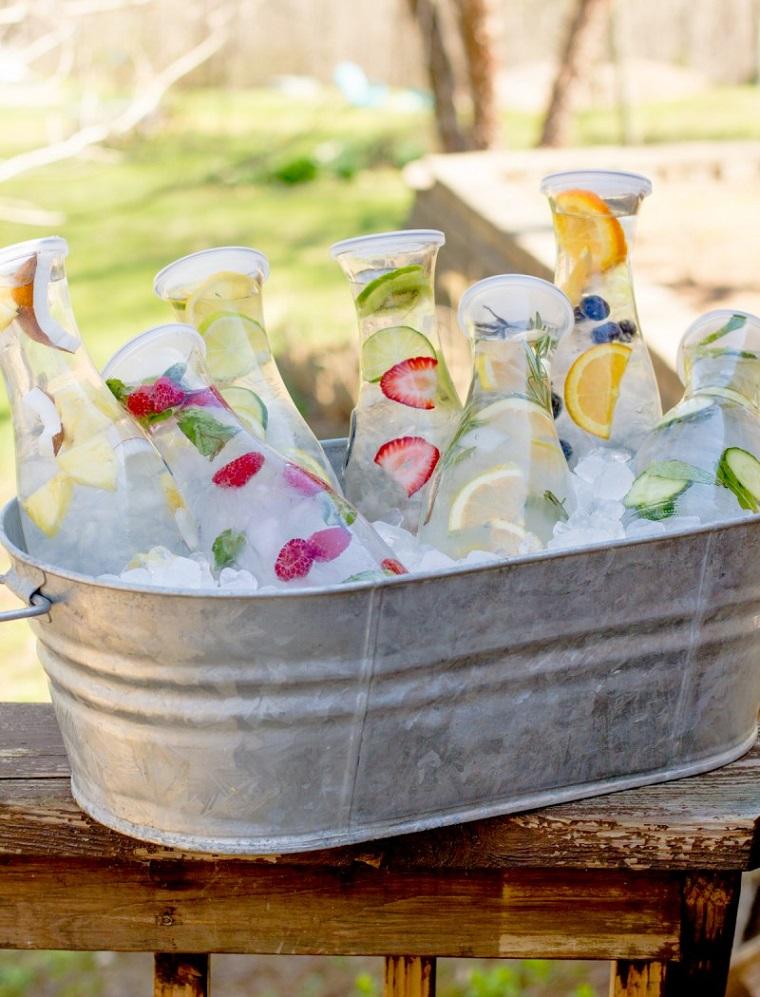 Ricette sgonfia pancia a base di acqua e frutta, bottiglie di vetro in un secchio metallico con ghiaccio