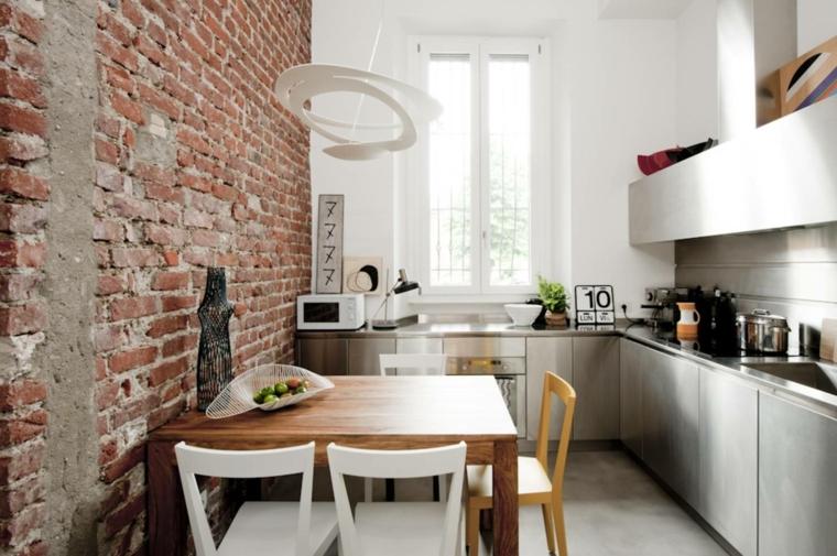 picca cucina con mobili in acciaio inox, tavolo in legno quadrato e interni in pietra