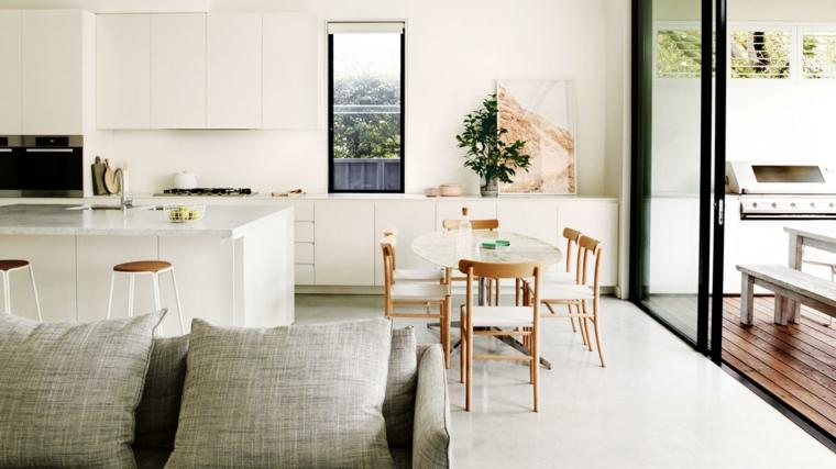 ambiente unico con cucina con mobili bianchi, tavolo ovale con sedie in legno, porta vetrata
