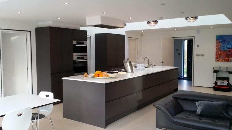 arredamento open space moderni con grande isola grigia con top bianco, tavolo bianco e divano nero