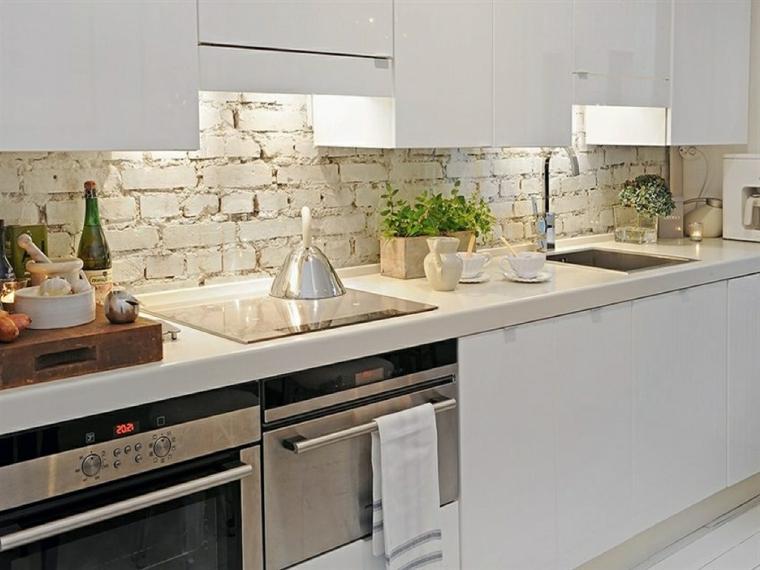 mobili laccati della cucina bianchi con elettrodomestici in acciaio inox e rivestimento parete pietra