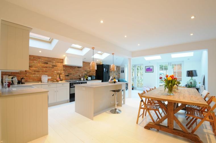 ampia e moderna cucina con isola e tavolo da pranzo con vaso e fiori e parete interna in pietra