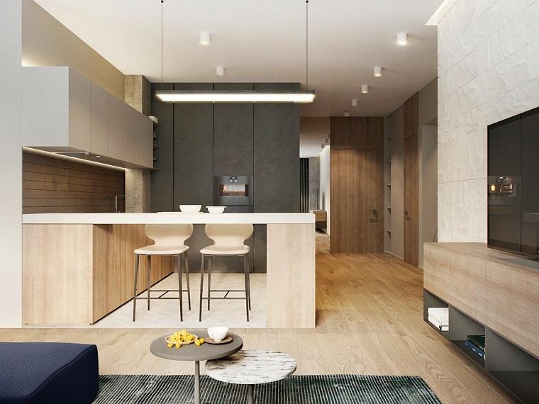 Open space cucina soggiorno, arredamento cucina con isola laterale e due sgabelli alti di colore bianco