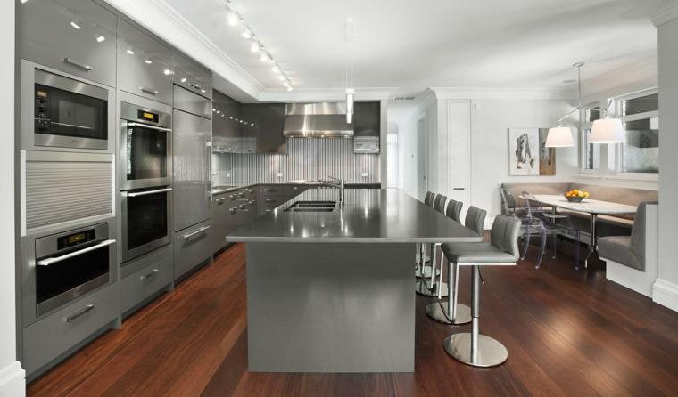 pavimento in parquet scuro, cucina grigia a l con elettrodomestici incassati, isola con sgabelli in acciaio, tavolo per il pranzo in legno