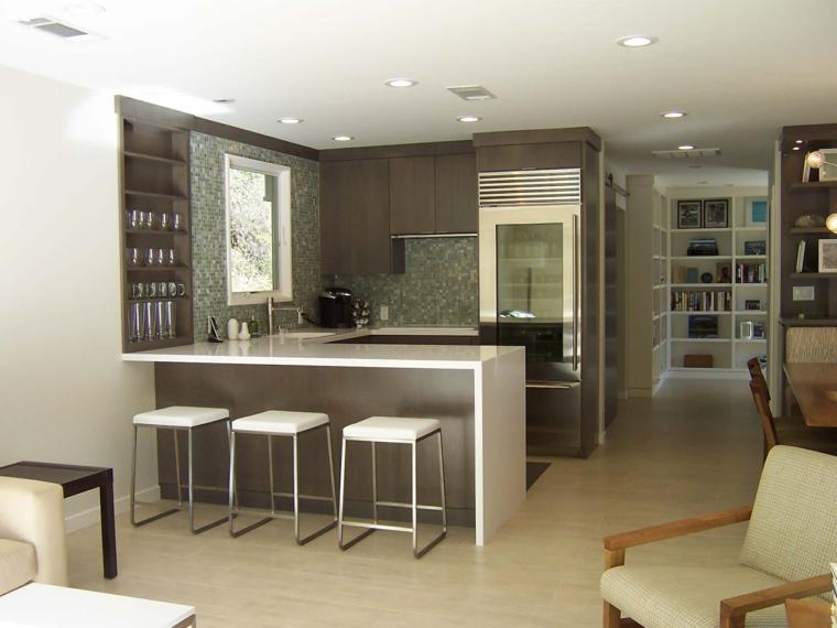 ambiente unico con cucina a u moderna bianca e marrone, divano e poltrone bianche, pavimento chiaro