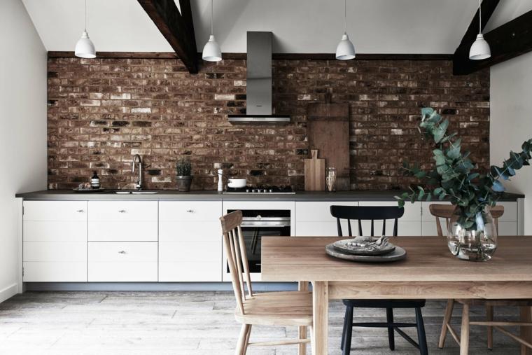 tavolo rettangolare in legno, cucina bianca lineare con cappa, lampadari a sospensione e interni in pietra