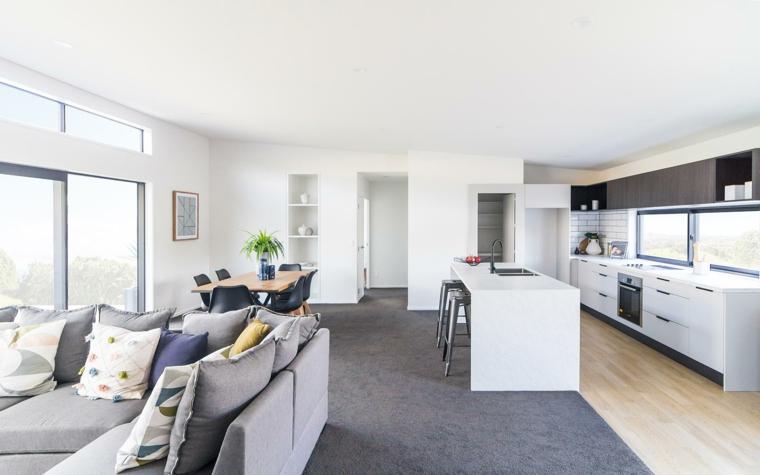 luminoso e ampio open space con mobili della cucina bianchi, divano grigio, grande tappeto grigio