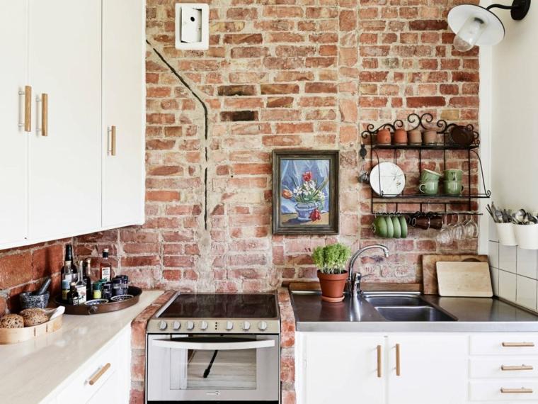 piccola cucina con mobili bianchi e maniglie in acciaio, mensole e quadro e pareti rivestite in pietra per interni