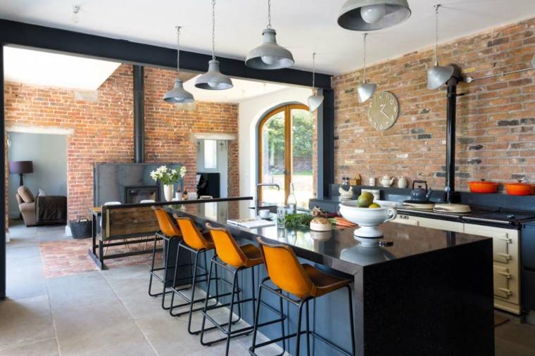 lampadari a sospensione e mobile della cucina con isola neri, sgabelli e pareti interne in pietra