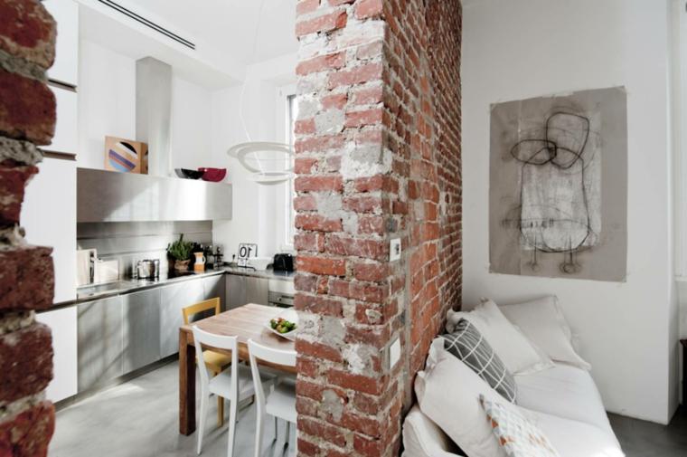 divano bianco con cuscini bianchi e grigi, cucina con mobili in acciaio e muri in pietra per interni