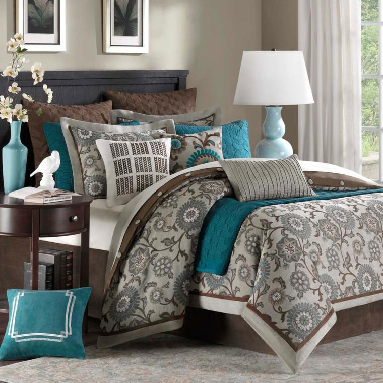 camera da letto con copriletto e cuscini tortora e turchese, comodino in legno, vaso con fiori bianchi