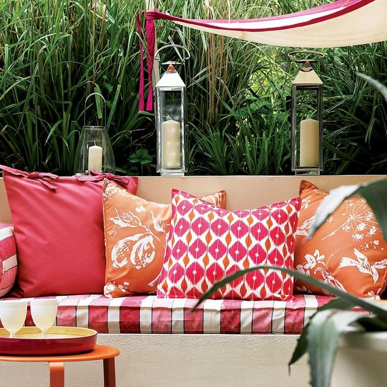 Decorazione giardino con un tanti cuscini colorati e portacandele di vetro molto grandi