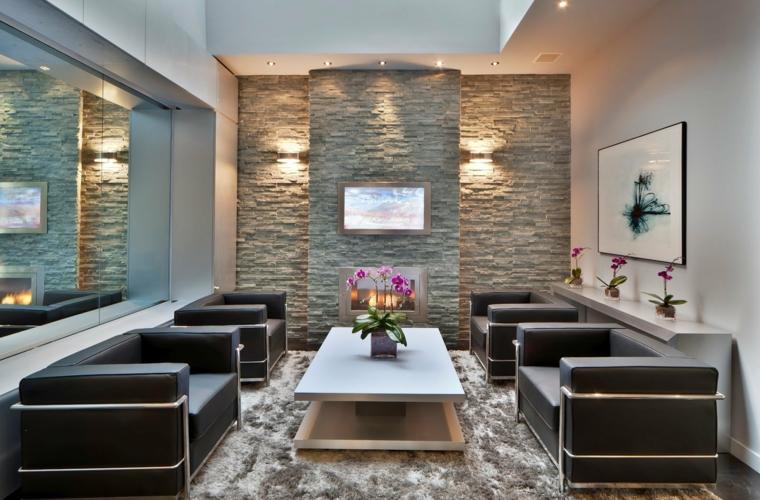 stretto e lungo soggiorno con poltrone in pelle nera e tavolino basso, parete rivestita con della pietra