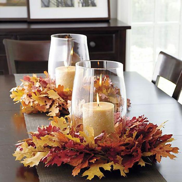 Addobbi tavola per l'autunno, centrotavola con portacandele di vetro e foglie secche come base