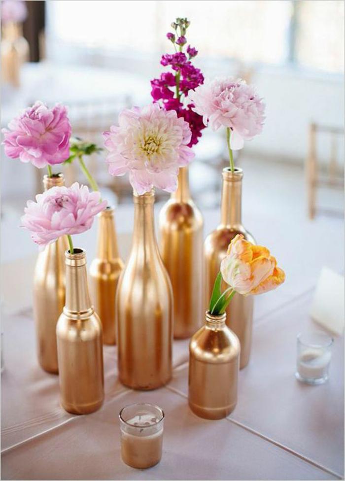 Addobbi tavola con bottiglie di vetro dipinte di colore oro e con dei fiori