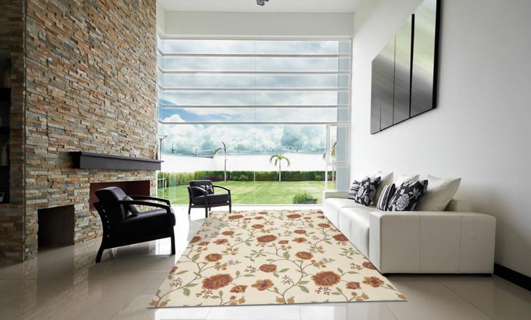 ampio e luminoso salotto con divani bianchi e poltrone nere, muro in pietra e grande vetrata