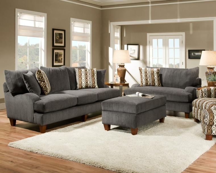 soggiorno con pavimento in parquet, tappeto bianco, divani e puff grigi e pareti color tortora chiaro
