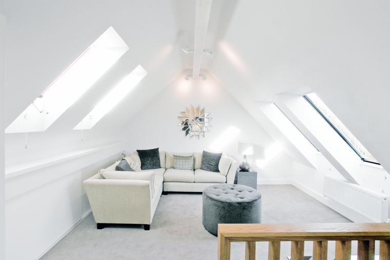 pareti e pavimento bianchi, divano angolare bianco con cuscini grigio chiaro e grigio scuro, puff tondo, come arredare una mansarda piccola