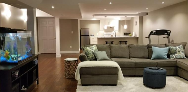 piccola cucina a vista con isola e sgabelli, divano color salvia, pavimento in parquet