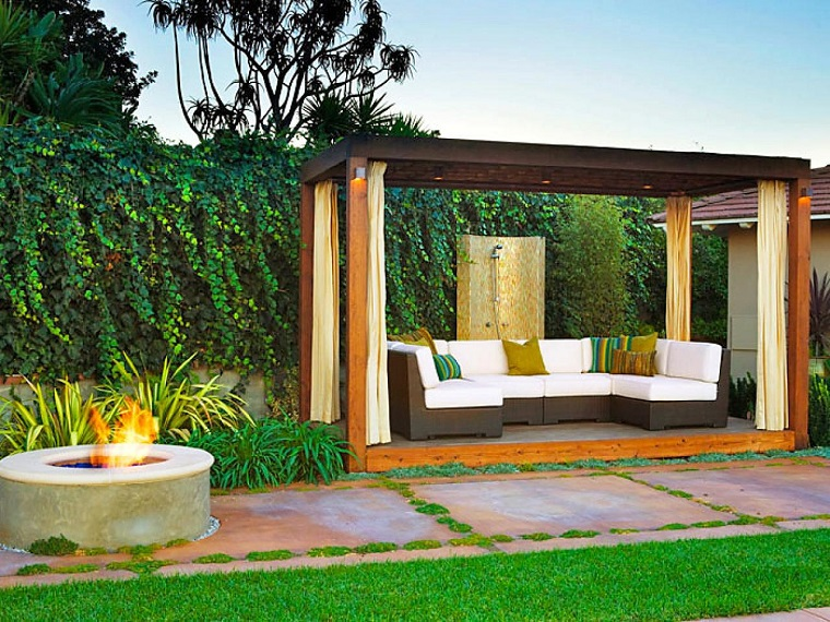 Piante ornamentali da giardino, pergola di legno con un divano in rattan e sudute di colore bianco
