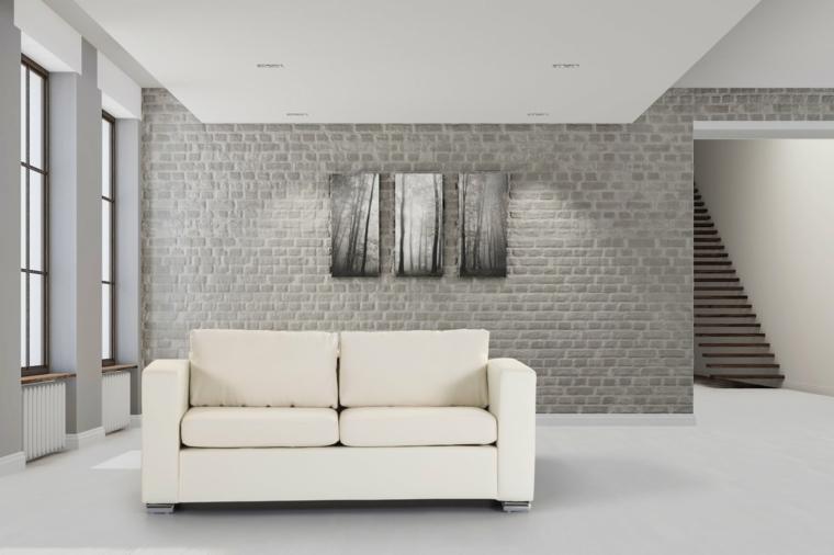 salotto dal design minimal con un divano a due posti bianco, tre quadri astratti e pareti rivestite in pietra per interni