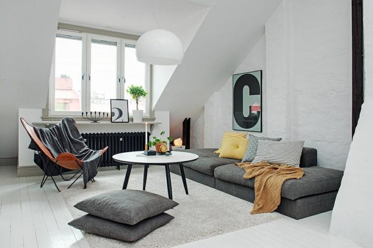 zona living con divano e cuscini a terra grigi, poltrona arancione con plaid grigio. arredare mansarda moderna